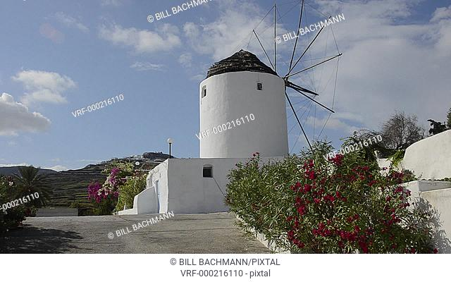 White windmill house in town in valley of Fira in Santorina Greece in Greek Islands