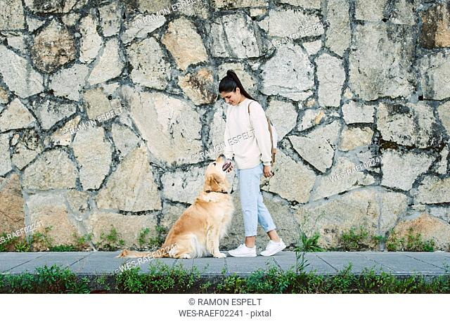 Young woman with her Golden retriever dog at a stone wall