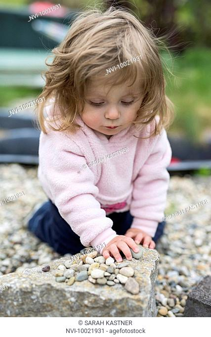 Little girl playing with pebbles