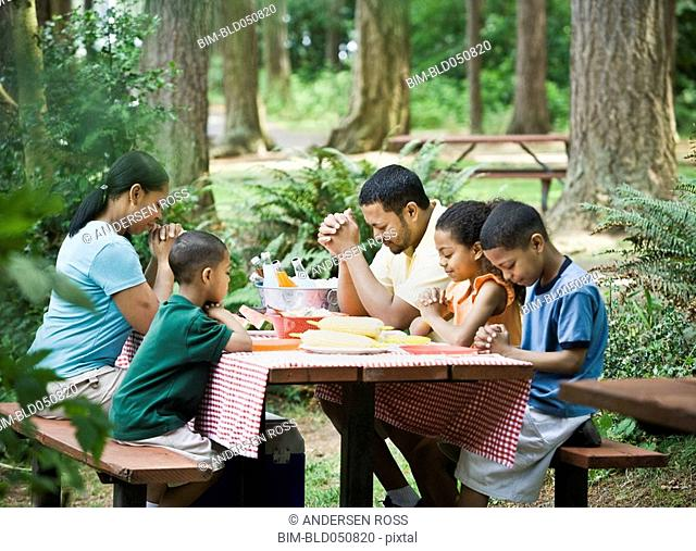 Multi-ethnic family praying at picnic table