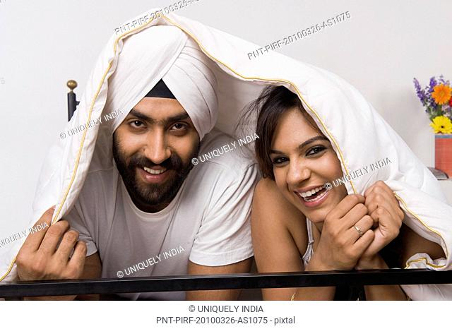 Sikh couple covering themselves with a blanket