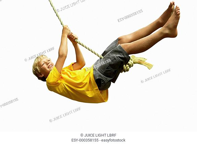 Boy swinging on rope swing, smiling, side view, cut out