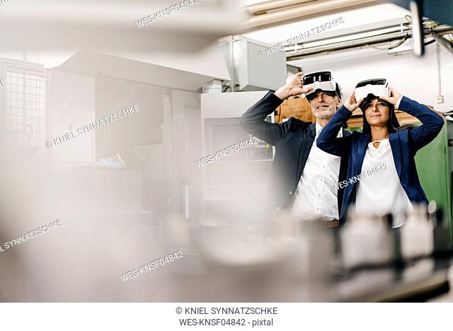 Businessman an woman in high tech enterprise, using VR glasses