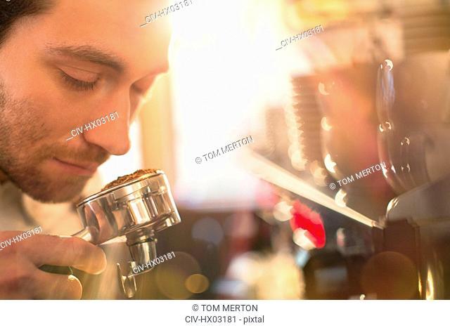 Close up barista smelling espresso grounds at espresso machine