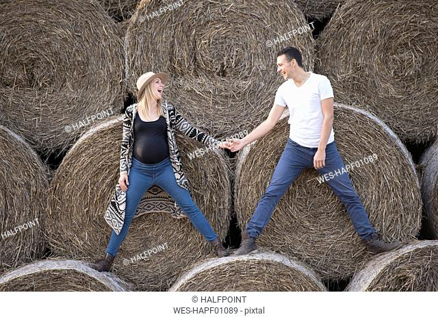 Happy expectant parents standing on bales of straw