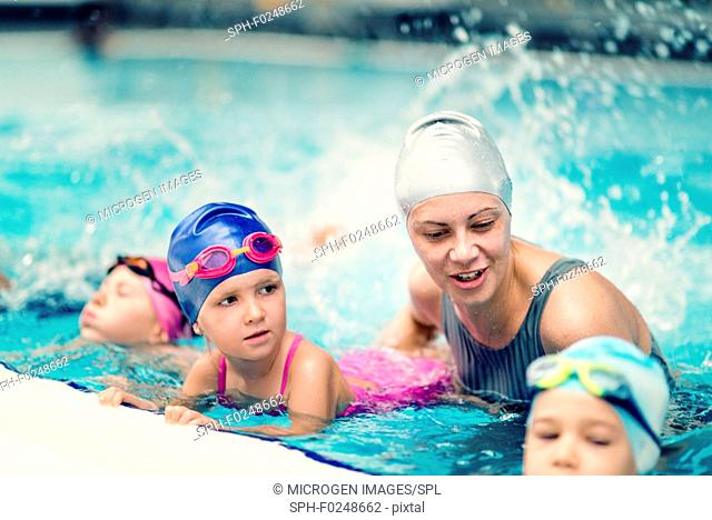 Swim school. Swimming instructor with group of children