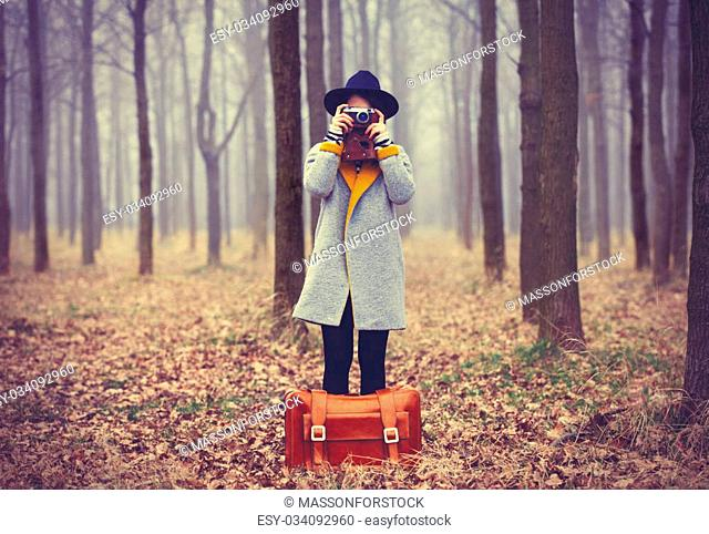 portrait of a young woman with a suitcase and camera standing in the middle of the forest