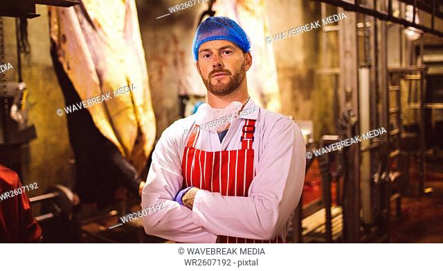 Portrait of butcher standing with arms crossed in meat storage room
