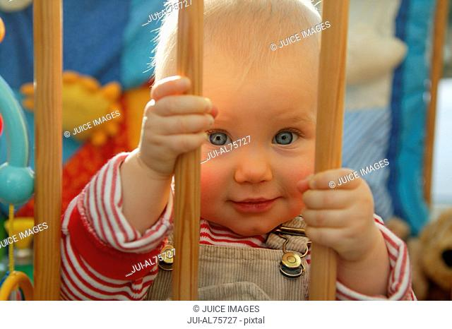 View of baby girl holding the bars of a crib