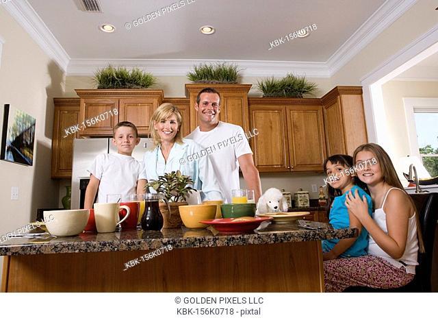 Portrait of family having breakfast in the kitchen