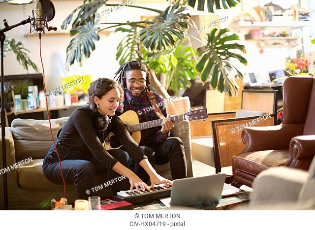 Young man and woman recording music, playing guitar and keyboard piano in apartment