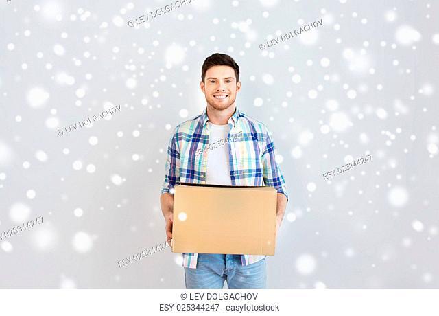 moving, delivery, housing, accommodation and people concept - smiling young man with cardboard box at home over snow
