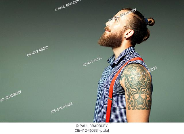 Curious hipster man with beard and shoulder tattoo looking up