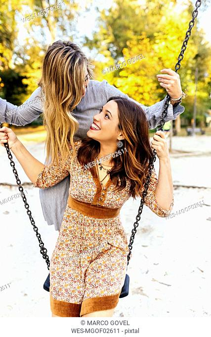 Two happy young women on a swing
