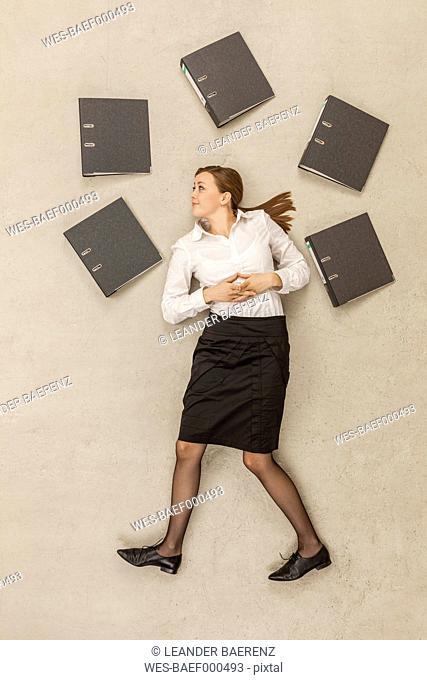 Businesswoman standing around files