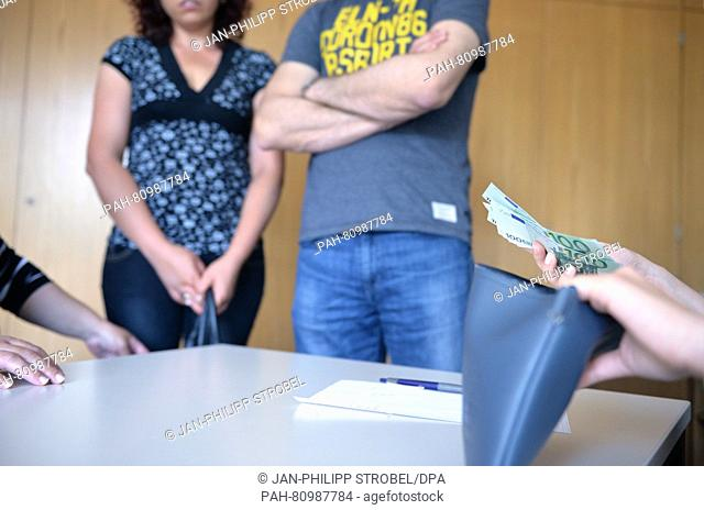 An employee hands money to storm victims at the Ostalb District Office inSchwaebisch Gmuend,Germany, 06 June 2016. People affected by the recent serious...