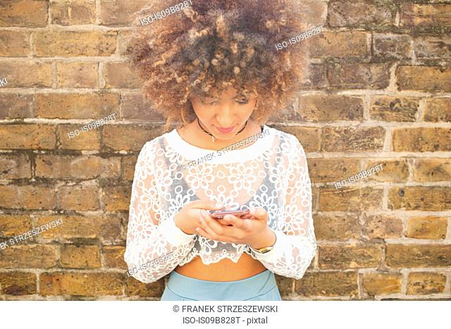 Young woman leaning against wall, using smartphone