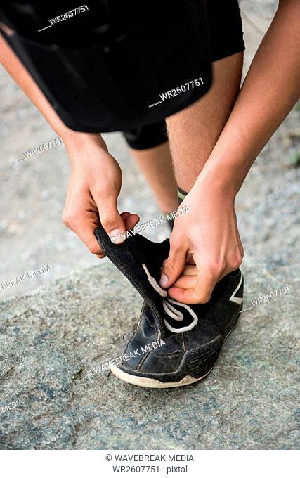 Male hiker tying shoelaces