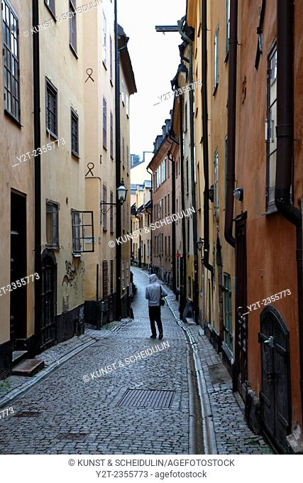 A hooded man walks down a narrow alley in Gamla Stan, the old town of Stockholm, Sweden