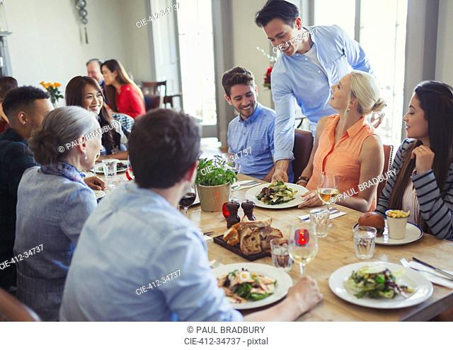 Waiter serving food to friends dining at restaurant table