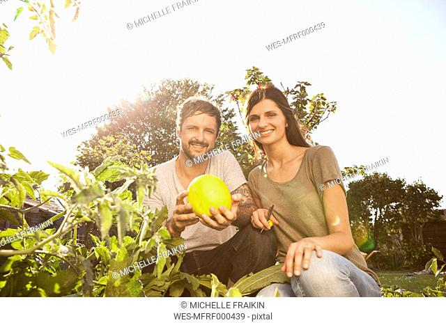 Smiling couple with yellow courgette in the garden