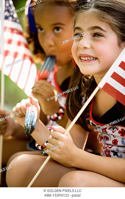 Girls eating popsicles waving US flags