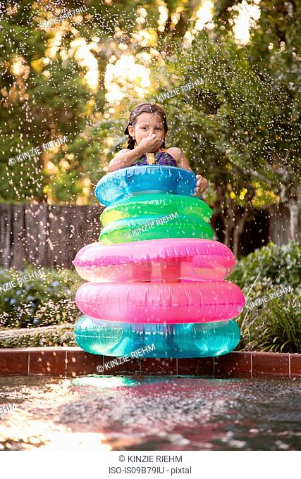Young girl, standing in the middle of inflatable rings on the side of outdoor swimming pool