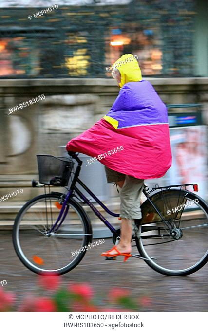 woman on bicycle in the rain with rain cape