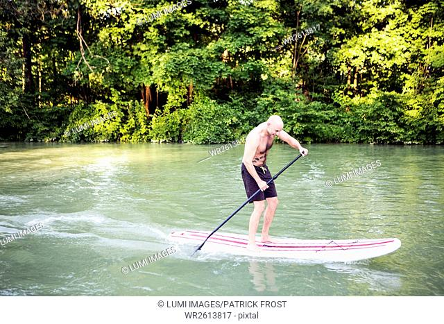 A man is paddling on a stand up paddle boat