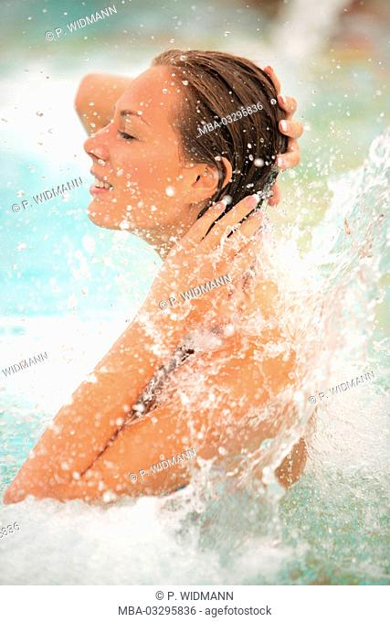 Young woman relaxes in a thermal bath