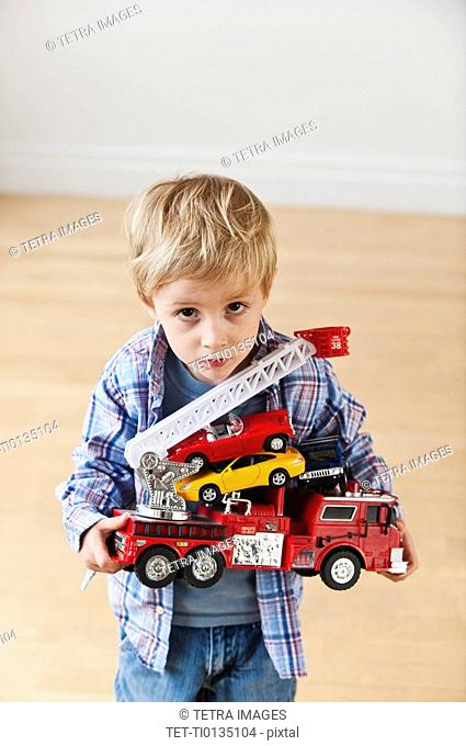 Portrait of boy 3-4 holding toy fire engine and cars