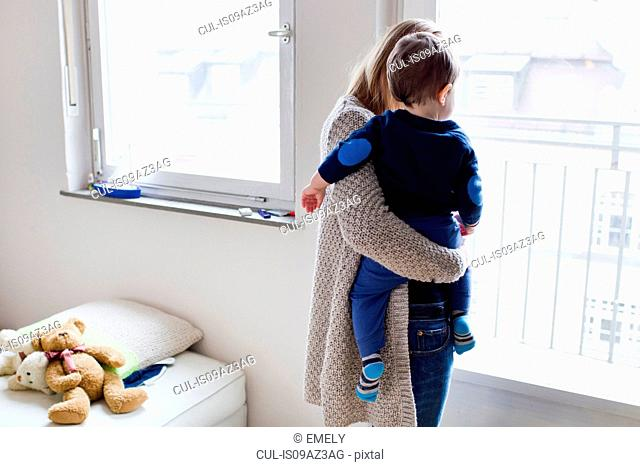 Rear view of mid adult woman and baby son looking through window
