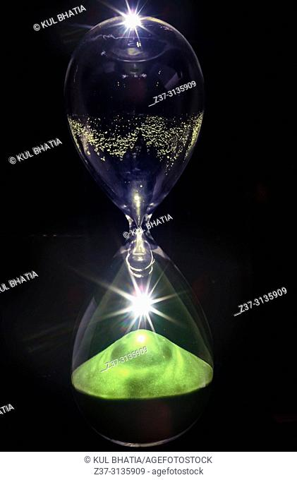 An hour glass, embellished with light flares, symbolizes enlightenment and passing time