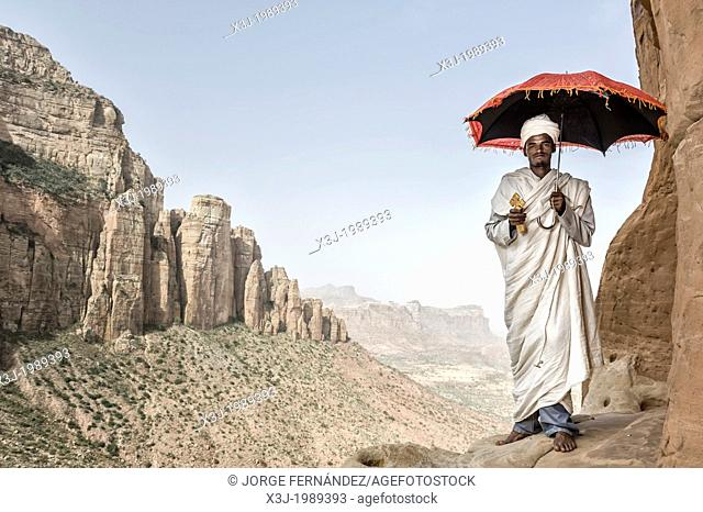 Priest standing on the path that leads to Abuna Yemata church. The access to this church is quite difficult since the last few meters you have to walk on a...