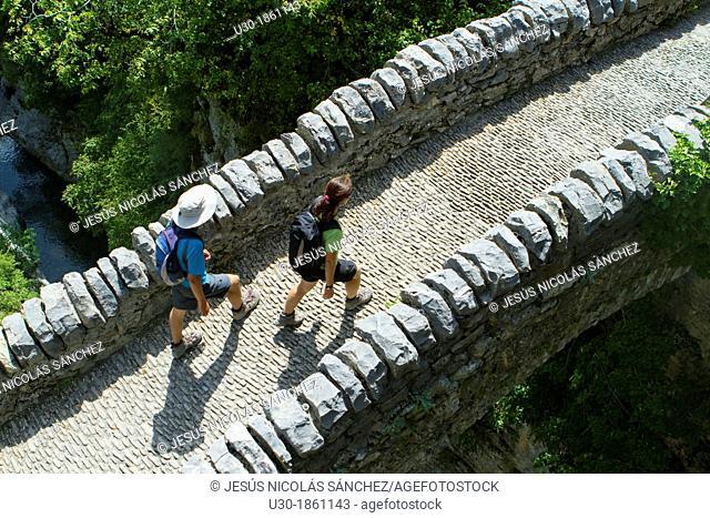 Hikers walking on San Urbez Bridge above Bellós river, in Añisclo Valley, canyon belonging to Ordesa y Monte Perdido National Park  Pyrenees  Fanlo  Huesca...