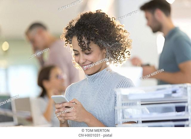 Smiling businesswoman texting with cell phone in office