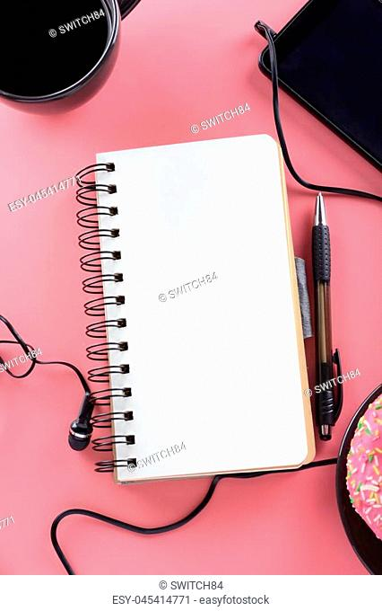 Open notebook on springs with white pages. Tablet, coffee and donuts. Disorder. Mock up