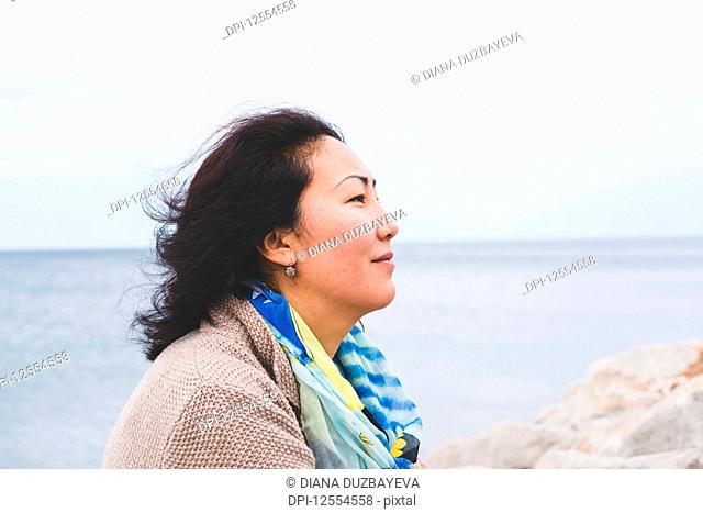 Portrait of the side view of a woman with the ocean in the background; Italy