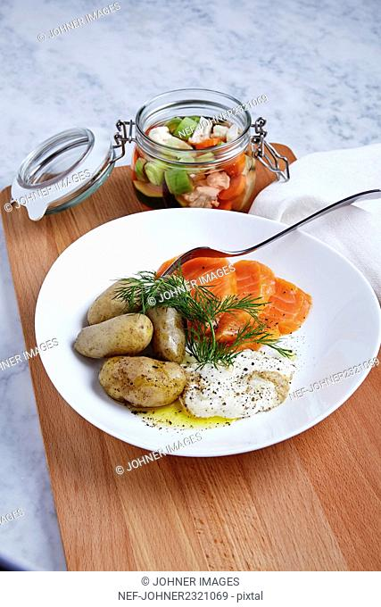Baked potatoes with fish on plate and salad in jar