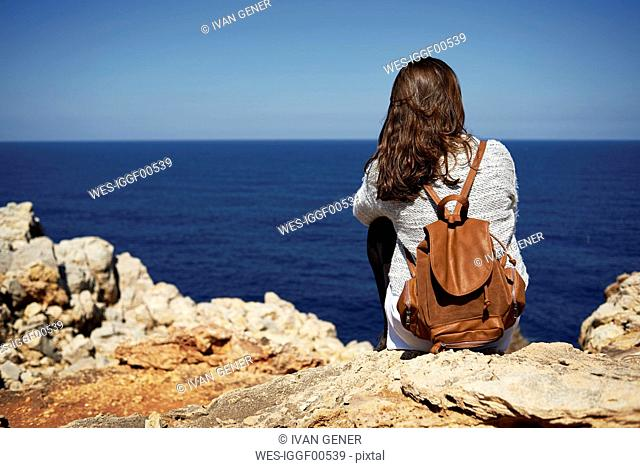 Young brunette woman sitting on coast, looking at view