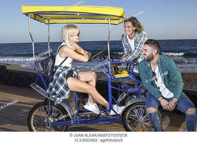 Cheerful men and woman friends sitting in cycle cart at seaside together. Lanzarote, Canary Islands, Spain