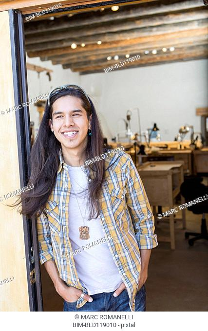Mixed race man standing in doorway of art studio