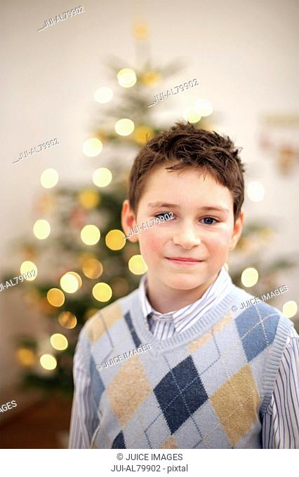 Boy with Christmas tree in background