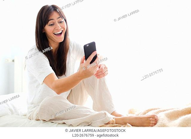 Woman using smartphone showing surprise