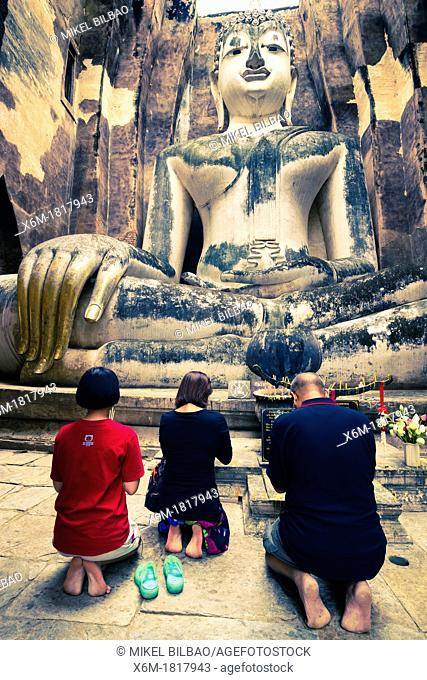 Believers in a Buddha statue  Wat Sri Chum  Sukhothai Historical Park  Thailand