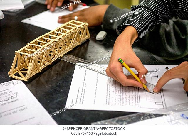 A high school student in Mission Viejo, CA, makes a mechanical drawing of a structural bridge model in a conceptual physics class