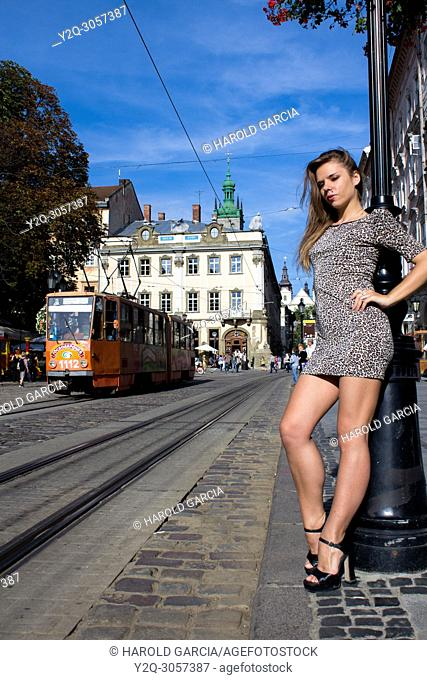 Sexy and thin Ukrainian woman wearing a leopard-skin print dress posing near the tram rail for a photographic sequence in the ancient city of Lviv, Ukraine