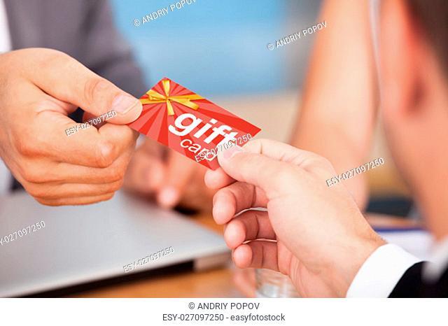 Close-up Of Two Businessmen Holding Card Over Desk