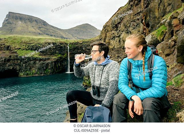 Hikers enjoying view from rocks, Gasadalur, Vagar, Faroe Islands