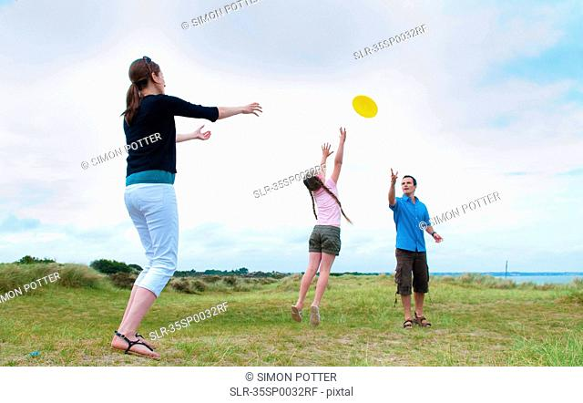Family playing with flying disc outdoors